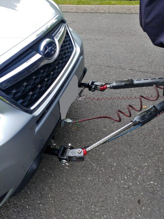 Tow bar attached to direct connect pins with safety cables, breakaway cable, and electrical connection attached. The tow bar is compressed ready for the drag-it-forward step of my checklist.