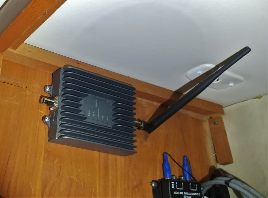 Surecall Cell Phone booster during installation in my electronics cabinet with whip antenna.