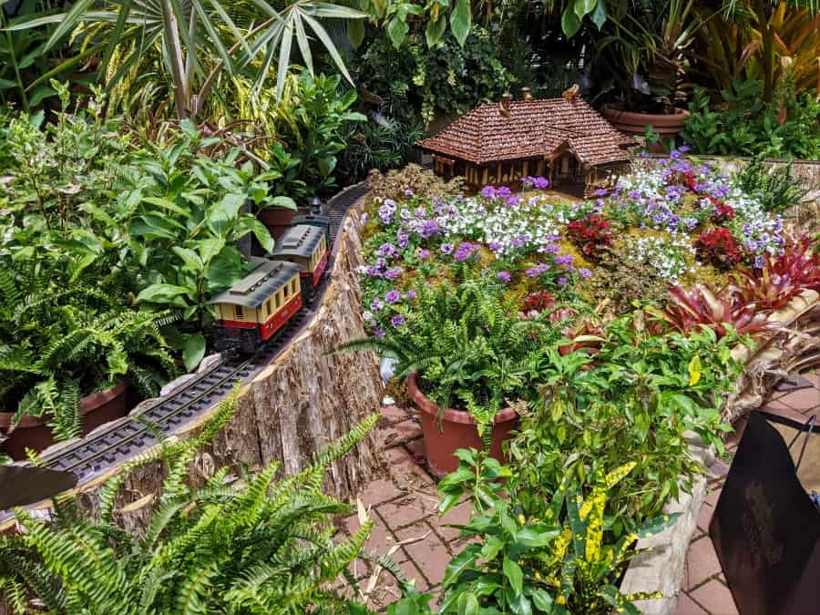 Inside the Biltmore Conservatory of the model train and a model of the landscapers home.