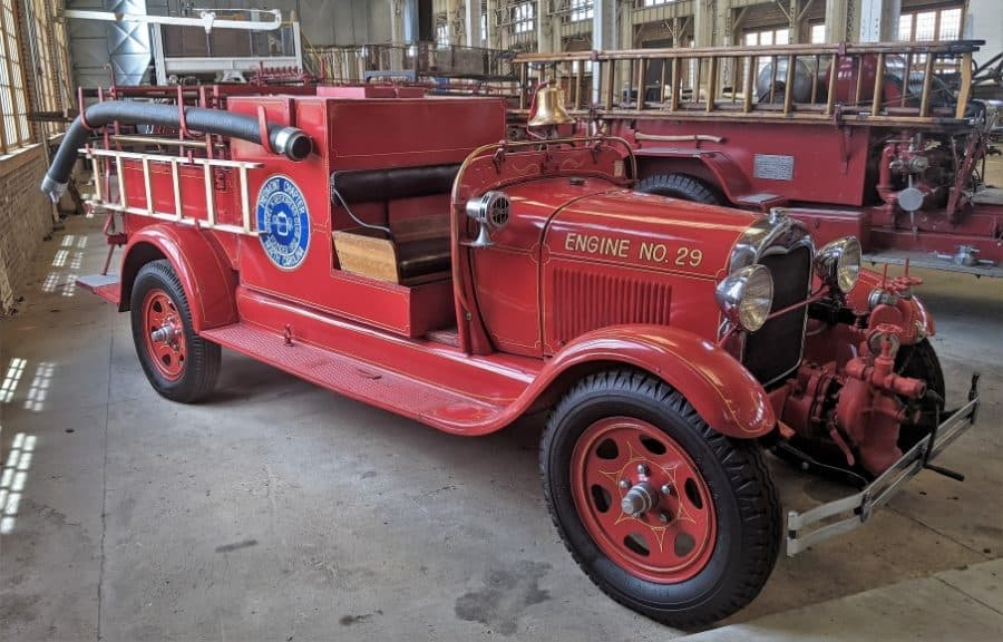 Ford Model AA Pumper truck next to a hook and ladder truck.